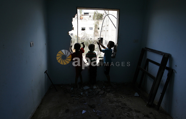 "Palestinian children play in a destroyed house in Khan Yunis in the southern Gaza Strip on September 11, 2014. Israel's deputy foreign minister,Tzahi Hanegbi , warned that Hamas was likely to resume ""violence"" if it feels it has made no political gains from upcoming talks in Cairo. Photo by Abed Rahim Khatib"