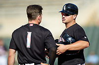 Kannapolis Intimidators manager Justin Jirschele (9) talks to Tyler Frost (1) between innings of the game against the Hagerstown Suns at Kannapolis Intimidators Stadium on May 6, 2018 in Kannapolis, North Carolina. The Intimidators defeated the Suns 4-3. (Brian Westerholt/Four Seam Images)