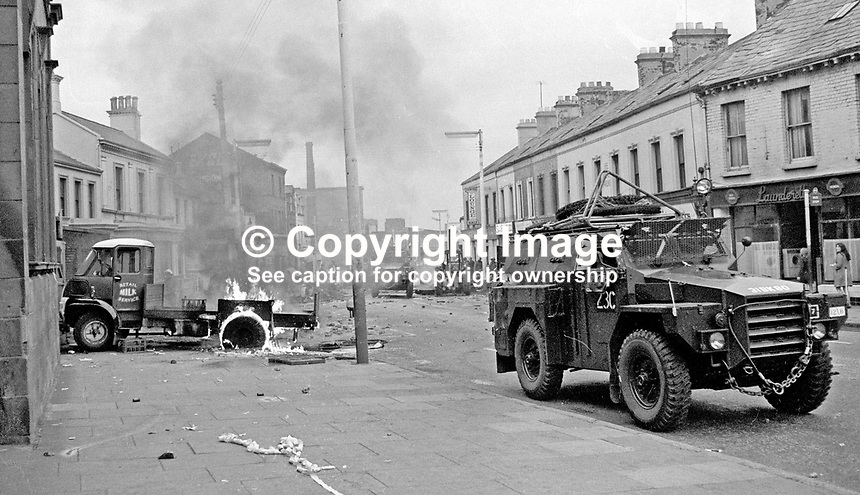 An army personnel carrier patrolling a debris-strewn street passes a burning milk delivery lorry. 197007030251a...The British Army imposed during July 3 &amp; 4, 1970, a 34 hour curfew (except for a two hour break to allow shopping) in approximately 50 streets in the Lower Falls district of Belfast, N Ireland, UK. A military helicopter hovers overhead warning people they would be arrested if they remained on the streets. An army search during the curfew uncovered 100 firearms, 100 home-made bombs, 250 lbs of explosives, 21000 rounds of ammunition and 8 two-way radios. This curfew is often seen as a turning point in souring relations between the Roman Catholic working class and the British Army. The army was no longer seen as the protector of the Catholic community.<br /> <br /> Copyright Image from Victor Patterson, 54 Dorchester Park, Belfast, UK, BT9 6RJ<br /> <br /> t: +44 28 90661296<br /> m: +44 7802 353836<br /> vm: +44 20 88167153<br /> e1: victorpatterson@me.com<br /> e2: victorpatterson@gmail.com<br /> <br /> For my Terms and Conditions of Use go to www.victorpatterson.com