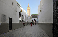 Access corridor to the Mausoleum of Moulay Idriss I, running alongside a courtyard (through the horseshoe arches) and with the minaret above, Moulay Idriss, Meknes-Tafilalet, Northern Morocco. The mausoleum was rebuilt by Moulay Ismail, 1672-1727, in the 17th century and is the site of an important moussem or pilgrimage festival each summer. The town was founded by Moulay Idriss I, who arrived in 789 AD and ruled until 791, bringing Islam to Morocco and founding the Idrisid Dynasty. His body was moved to a tomb in the mausoleum. Picture by Manuel Cohen