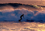 A California surfer rides the foam of a crashing wave.