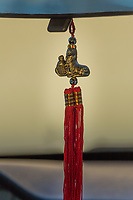 A Lunar New Year decoration hanging from a car's rearview mirror - a dog, honoring The Year of the Dog, with a bright red tassel below.