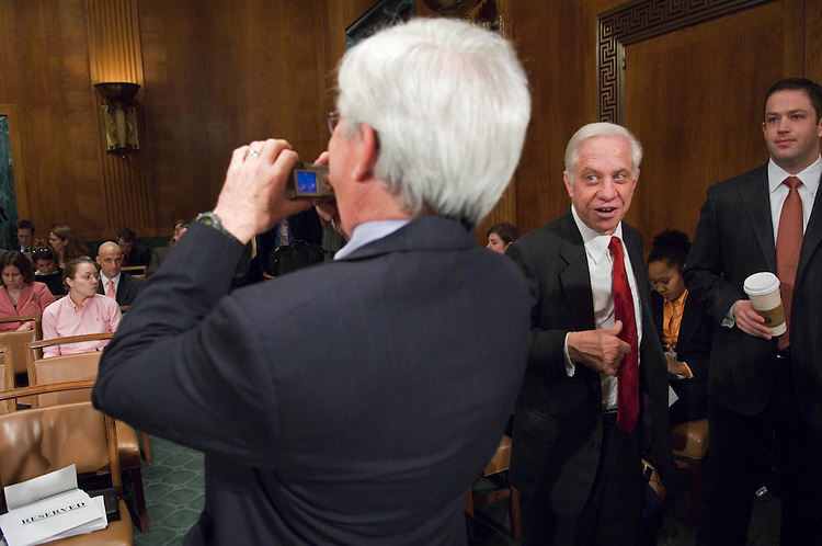 """03/10/06.VICTOR E. SCHWARTZ--As fellow witness Professor Frank J. Vandall, of the Emory School of Law, takes a picture of the audience before the hearing, Victor E. Schwartz, second from right, a partner with Shook, Hardy & Bacon LLP in Washington, DC, and counselor to the National Restaurant Association, tells a story to Blain Rethmeier and other committee aides before testifying during the Senate Judiciary hearing titled, """"Defective Products: Will Criminal Penalties Ensure Corporate Accountability?"""" Vandall and Schwartz last saw each other about nine years ago; they have known each other for about 20 years..CONGRESSIONAL QUARTERLY PHOTO BY SCOTT J. FERRELL"""
