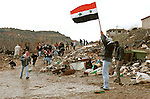 Waving the Syrian flag, Druze youth dodge rubber bullets as they clash with Israeli border police, in the Druze village of Majdal Shams, Golan Heights, in the year 2000.
