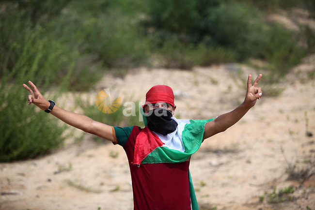 A Palestinian protester flashes victory sign during clashes with Israeli security forces next to the border fence with Israel, at the Erez crossing in the northern Gaza strip, on October 13, 2015. A wave of stabbings that hit Israel, Jerusalem and the West Bank this month along with violent protests in annexed east Jerusalem and the occupied West Bank, has led to warnings that a full-scale Palestinian uprising, or third intifada, could erupt. The unrest has also spread to the Gaza Strip, with clashes along the border in recent days leaving nine Palestinians dead from Israeli fire. Photo by Ashraf Amra