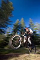 Dave Fafard pop a wheelie on mountain bike, Alberta, Canada