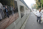 Nov 10, 2009 - Tokyo, Japan - A Japanese factory worker looks at the large pictures depicting the collapse of the Berlin Wall along the wall of the German Embassy in Tokyo.