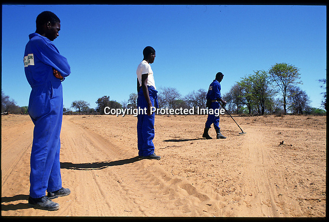 diangol00427. Angola Cunene Province. Sappers with German humanitarian demining NGO, Cap Anamur, near Xangongo, , walk in a row behind the man with the metal detector into a suspest area, in their mission to clear landmines, and other explosives, left behind during the civil war .11/93.© Rodger Bosch/iAfrika Photos