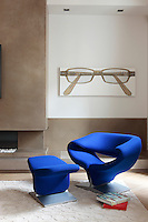 "Beside the concrete fireplace in the living room hangs ""Brille"" a painting by René Wirths; the blue ""Ribbon"" chair and footstool are Pierre Paulin designs"