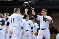 Right fielder Cody Brittain (18) of the University of South Carolina Upstate Spartans, right, is congratulated at home plate by Jake Beaver (11) after hitting a home run in the first inning of a game against the Winthrop University Eagles on Wednesday, March 4, 2015, at Cleveland S. Harley Park in Spartanburg, South Carolina. Upstate won, 12-3. (Tom Priddy/Four Seam Images)
