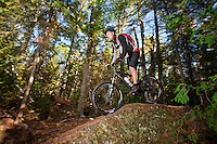 Riding over natural rock features while mountain biking in Copper Harbor Michigan Michigan's Upper Peninsula.