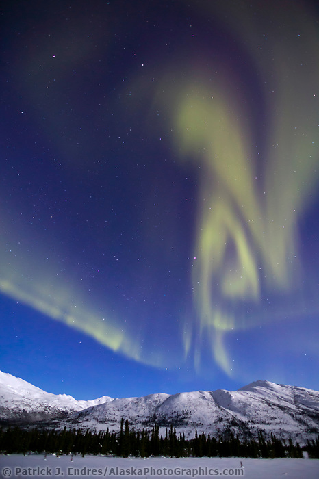 Aurora borealis swirls across the sky over the Brooks Range, Arctic Alaska.