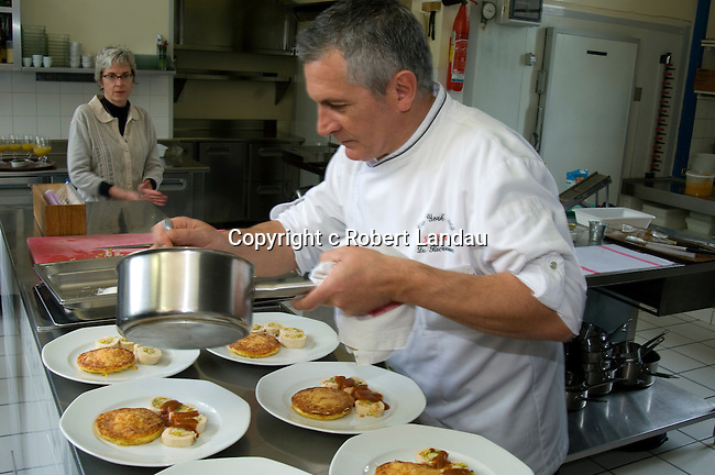 Chef Jacques Ratier of the restaurant La Receration in Les Arques, France puts the finishing touches on a dish during a small cooking class for visitors.