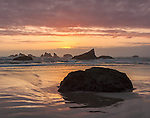 Bandon State Park, OR: Sunset clouds and reflections at low tide with silhouetted seastacks at Bandon Beach