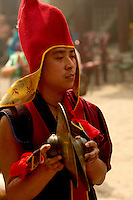 Buddhist Lama Monk carrying cymbals as part of a band in a Losar Procession from the Himalayan region.