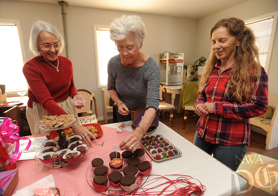 NWA Democrat-Gazette/ANDY SHUPE<br /> Jeffi O'Kane (from left), Jane Bryant and Mim Heinrichs, all volunteers with the Friends of the West Fork Library, set up Thursday, Feb. 9, 2017, for the first Valentine Chocolate Buffet in Library Hall north of the library in West Fork. The buffet is planned for 10 a.m. to noon Saturday and will feature locally made chocolate items in a special Valentine's Day box for a $10 donation to the group. Among other projects, the Friends are working to fund an addition to the library.