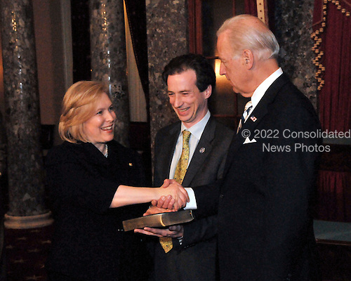 Washington, DC - January 27, 2009 -- United States Senator Kirsten Gillibrand (Democrat of New York), left, shakes hands with United States Vice President Joseph Biden after recreating her swearing-into office in the Old Senate Chamber of the United States Capitol in Washington, D.C. on Tuesday, January 27, 2009.  Her husband Jonathan holds the Bible..Credit: Ron Sachs / CNP.(RESTRICTION: NO New York or New Jersey Newspapers or newspapers within a 75 mile radius of New York City)