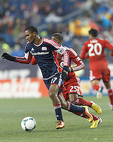 New England Revolution forward Jerry Bengtson (27) clears the ball as Toronto FC midfielder Jeremy Hall (25) closes. In a Major League Soccer (MLS) match, the New England Revolution (blue) defeated Toronto FC (red), 2-0, at Gillette Stadium on May 25, 2013.