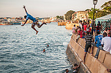 ZANZIBAR, Stone Town, a boy is jumping to the Water from one of the  City's Wall