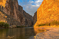Santa Elena Canyon Glow -Sunrise glow over the Santa Elena Canyon cliffs cast this nice orange glow right after the sun came up this morning along with these nice reflections in the Rio Grande river as it flow out of mountains that separate Texas from Mexico.  This Texas landscape had a nice blue sky with some nice clouds along with the morning colors with the river rocks just leading you inside the canyon as the river flow out the mouth of the canyons. To me the Santa Elena Canyon are one of the highlights of the Big Bend National park, to get there it is about an hour drive on the Ross Maxwell Scenic drive west through the Chiso Mountain when almost to the end of the road, there is an scenic overlook of the canyon landscape from here. But if you want explore more drive a little farther to the trail head where you can walk about 5 minutes along a board walk on sand to get to a beach area where the Rio Grande River flows out of the mouth of the canyons.  If you like you can climb up the cliffs to there are several fairly accessable views points for some outstanding Texas scenery that are not too high or difficult to climb or stay below and enjoy the stunning view from below. The river is seldom too deep and in some cases you can walk quite a ways back into the canyons.   We have landscape images from several views of this wonderful Texas scenery on our site beecreekphoto.com