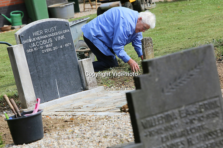Foto: VidiPhoto<br /> <br /> VALBURG - Gemeentedag op het kerkhof in Valburg (Gelderland). Leden van de hervormde gemeente Valburg-Homoet trokken zaterdag massaal naar de begraafplaats van de kerk voor een gezamenlijke schoonmaakdag. De paden van dodenakker Rustoord waren door het groeizame weer overwoekerd met onkruid en ook de verouderde graven moesten dringend een schoonmaakbeurt hebben. De armlastige en kleine gemeente besloot een oproep te doen in het kerkblad met als gevolg dat een groot deel van de gemeente -jong en oud- zaterdag de handen uit de mouwen stak om onder leiding van de plaatselijke predikant in &eacute;&eacute;n ochtend tijd de hele begraafplaats op te knappen. Dat lukte.