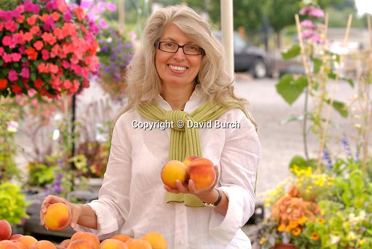 Mature woman holding peaches, portrait, smiling
