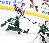 Bemidji State's Aaron McLeod tries to block the puck from reaching goalie Dan Bakala as UNO's Rich Purslow closes in during the first period. Bemidji State beat UNO 4-2 Friday night during the first round of the WCHA playoffs at Qwest Center Omaha. (Photo by Michelle Bishop)