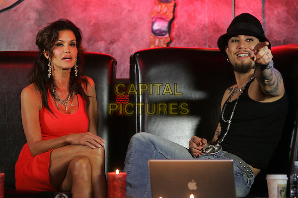 JANICE DICKINSON & DAVE NAVARRO .During episode 2 of Dave Navarro's weekly internet TV show, Spread Entertainment on Maniatv.com featuring Janice Dickinson held at The Dragonfly in Hollywood, California, USA..half 3/4 length sitting red dress legs crossed jeans denim black top tattoos hat goatee facial hair  pointing hand .May 24th, 2007.CAP/DVS.©Debbie VanStory/Capital Pictures