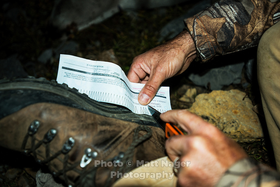 Outdoor Life Editor Andrew McKean prepares to tag his mule deer after a hunt on Greyback Ridge in the Hoeback Drainage of Wyoming Region H, outside of Alpine, Wyoming, September 21, 2015.<br /> <br /> Photo by Matt Nager