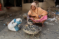 A woman sorts through electronics waste in the small village of Sangrampur, located near the city of Kolkata, India. November, 2013