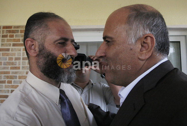 Former West Bank preventive security Fatah chief Jibril Rajoub (R) welcomes Naif al-Rajoub (L), one of several Hamas MPs arrested by Israel after Gaza militants captured an Israeli soldier in a deadly cross border raid in June 2006, following his release from prison at his home in Dora, near the southern West Bank town of Hebron.  Photo by Mamoun Wazwaz