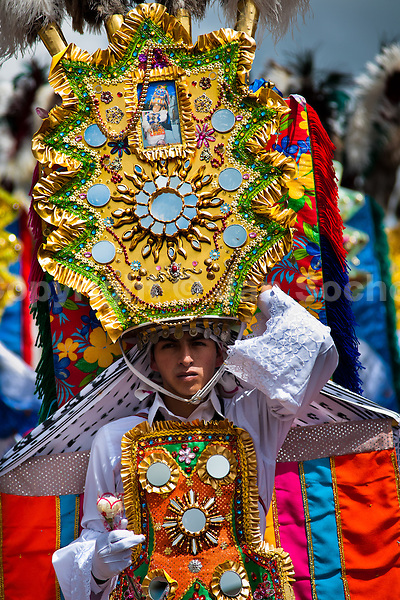 A dancer (danzante) performs in the religious parade within the Corpus Christi festival in Pujilí, Ecuador, 1 June 2013. Every year in June, thousands of people gather in a small town of Pujili, high in the Andes, to celebrate the Catholic feast of Corpus Christi. Introduced originally during the Spanish conquest of South America, this celebration merges Catholic rituals of Holy Communion with the traditional Andean harvest and sun festivities (Inti, the Inca sun god). Women dancers perform wearing brightly colored costumes while men dancers wear chest ornaments and heavy elaborate headdresses adorned with mirrors, jewelry, or natural items (shells). Being a dancer in the Corpus Christi ceremonial parade (El Danzante) is considered an honour and a privilege by the indigenous people in Ecuador.