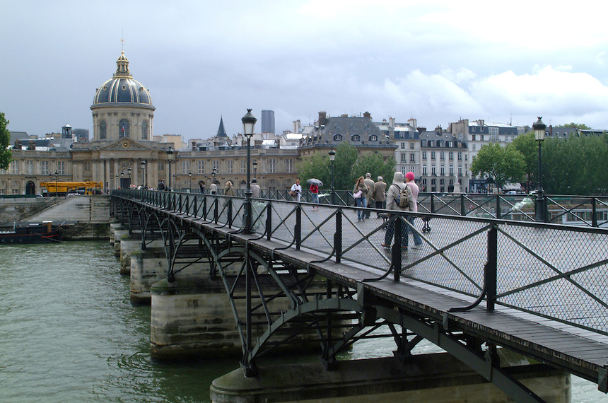 People going across the Walking Bridge over the Seine with the French Senat in the background on a rainy day in Paris, France; 2006.