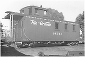 End-side view of long caboose #04343, flying herald, round roof at Alamosa.<br /> D&amp;RGW  Alamosa, CO  Taken by Polkinghorn, R. S. - 10/1950