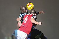 Adebayo Akinfenwa of Wycombe Wanderers and Dean Winnard of Morecambe in an aerial battle during the Sky Bet League 2 match between Wycombe Wanderers and Morecambe at Adams Park, High Wycombe, England on 12 November 2016. Photo by David Horn.