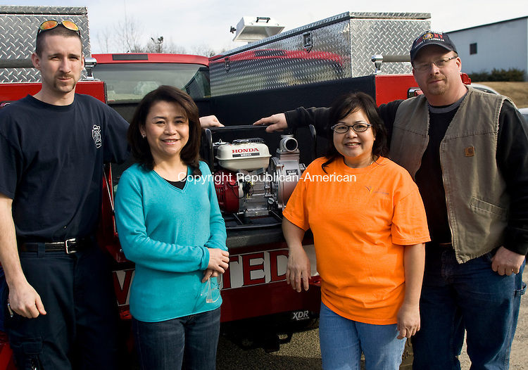 WINSTED, CT - 10 MARCH 2010 -031010JT02-<br /> From left, Winsted Fire Department Firefighter Adam Smith, Alcoa Howmet quality tech Pam Phonvichith, WFD Asst. Chief David Sartirana and Alcoa blender Chan Lothi pose for a photo with the department's new gas-powered portable water pump it bought with a $350 donation from a fundraiser selling egg rolls at Alcoa made by Lothi, who said that she loves to cook and to share her Laotian-style food.  <br /> Josalee Thrift Republican-American