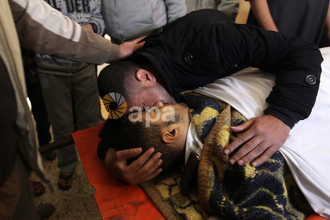 Palestinian relatives of Adnan Abu Khater, 16, mourn over his body during his funeral in Jabaliya refugee camp northern Gaza Strip January 03, 2013. Abu Khater died early Friday of wounds sustained by Israeli forces the day before at the Israeli border in the northern Gaza Strip, medical sources said. Photo by Ashraf Amra