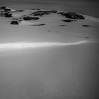 A snow covered landscape with footprints in the snow in eastern Greenland.