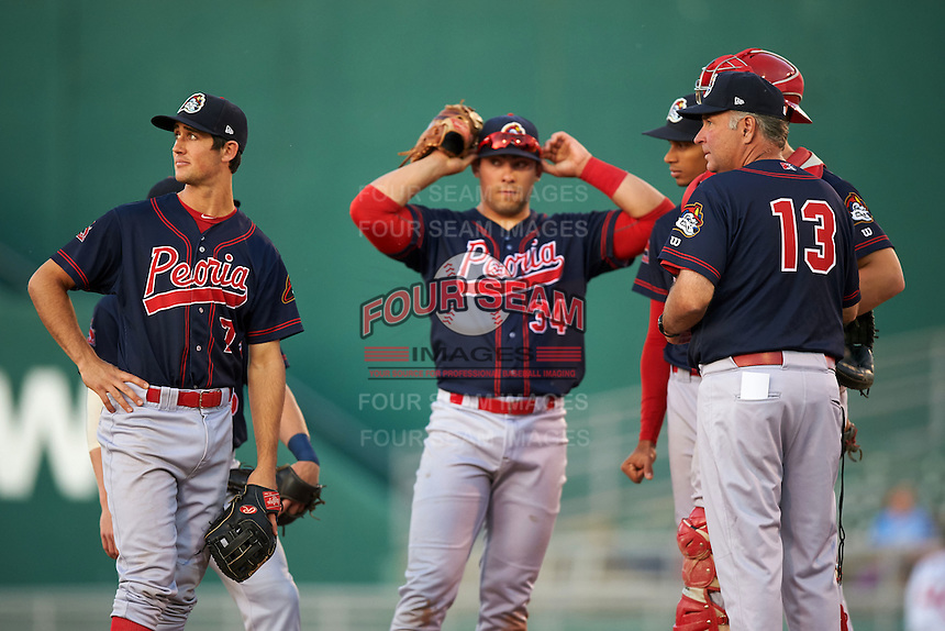 Peoria Chiefs manager Joe Kruzel (13) makes a pitching change with third baseman Danny Diekroeger (7), first baseman Alex De Leon (34) looking on during a game against the Lansing Lugnuts on June 6, 2015 at Cooley Law School Stadium in Lansing, Michigan.  Lansing defeated Peoria 6-2.  (Mike Janes/Four Seam Images)