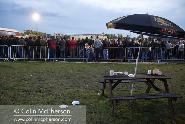 Discarded snacks in the home end as supporters watch the action during the second half of Stourbridge FC's match against visitors Biggleswade Town FC (green shirts) at the War memorial Athletic Ground in the FA Cup first round, a stadium which also doubles as a cricket ground. The match was won by the home side by four goals to one, watched by a capacity crowd of 1605. It was Biggleswade's first appearance at the first round stage of the cup, winners Stourbridge went on to play Stevenage in the second round.