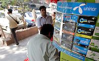 A street vendor selling subscriptions for telecom company Uninor. Telenor warned it could be forced to reconsider its presence in India if the New Delhi revises the terms of its spectrum licence amid a political scandal over regulation of the Indian telecoms industry.<br /> <br /> Unitech, since renamed Uninor, is one of five companies alleged to have benefited from irregularities that an official audit claimed had cost the Indian government $39bn in lost revenues from spectrum licences. <br /> <br /> Further reading : http://www.ft.com/cms/s/0/f391ebb0-33b4-11e0-b1ed-00144feabdc0.html#axzz1DWW1eUZh