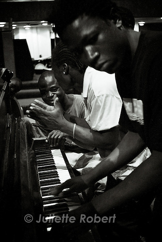 Some refugees play on an old piano inside the church.<br /> April 2009