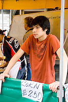 Young teen age 14 selling roasted corn on the cob. Grand Old Day Street Fair St Paul Minnesota USA