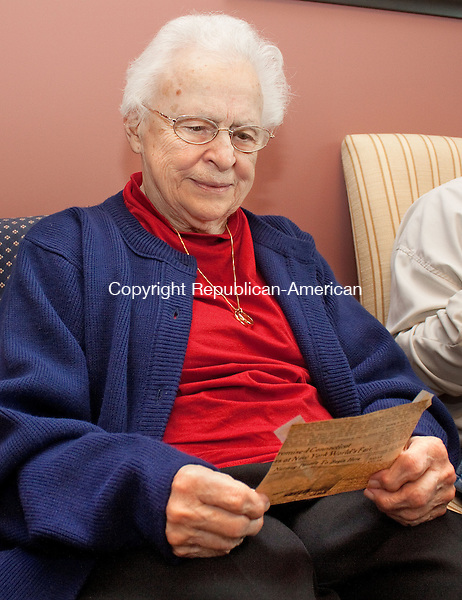 WATERBURY CT.-OCTOBER 16 2013 101613DA04- Violet Codianni, of Waterbury looks over a newspaper clipping of her graduating class of 1939 inside the building of what use to be East Mountain School in Waterbury which is now Employers Reference Source, Inc.Darlene Douty Republican American