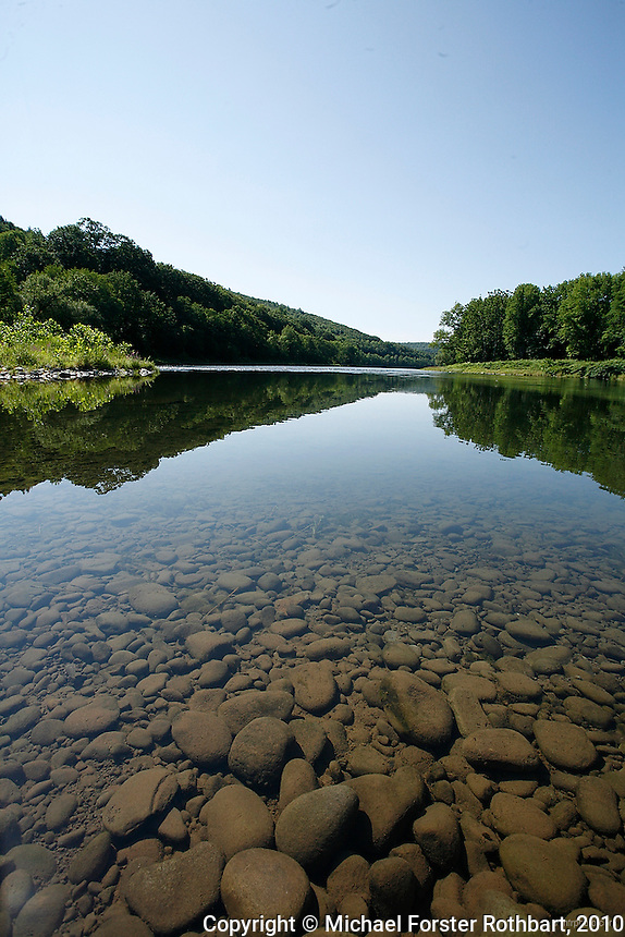 This view of the Upper Delaware River is at the mouth of Basket Creek, near Long Eddy, NY. The Upper Delaware Scenic and Recreational River, part of the National Park Service's Wild and Scenic Rivers System, stretches 73.4 miles along the New York - Pennsylvania border.<br /> <br /> Hydraulic fracturing or &quot;fracking&quot; is new method of drilling for natural gas: millions of gallons of water, sand and proprietary chemicals are pumped down a well under high pressure. The pressure fractures the shale, opening fissures so that natural gas can flow more freely. In August 2010, fracking is being widely used in the Marcellus Shale formation under Pennsylvania while New York considers a moratorium until the environmental effects can be reviewed. <br /> <br /> The 2005 Energy Policy Act exempted natural gas drilling from the Safe Drinking Water Act (plus some regulations of the Clean Water Act and Clean Air Act), and exempts companies from disclosing the chemicals used during fracking. Scientists have identified volatile organic compounds (VOCs) such as benzene, ethylbenzene, toluene, methane and xylene that have been found in contaminated drinking water near drilling sites. Other environmental concerns include surface water contamination, air pollution, forest fragmentation, plus human health problems. On the other hand, gas companies and property owners stand to earn up to one trillion dollars in profits from drilling in the Marcellus Shale.<br /> <br /> &copy; Michael Forster Rothbart<br /> www.mfrphoto.com <br /> 607-267-4893 o 607-432-5984<br /> 5 Draper St, Oneonta, NY 13820<br /> 86 Three Mile Pond Rd, Vassalboro, ME 04989<br /> info@mfrphoto.com<br /> Photo by: Michael Forster Rothbart<br /> Date: 8/2010    File#:  Canon 5D digital camera frame 68031.