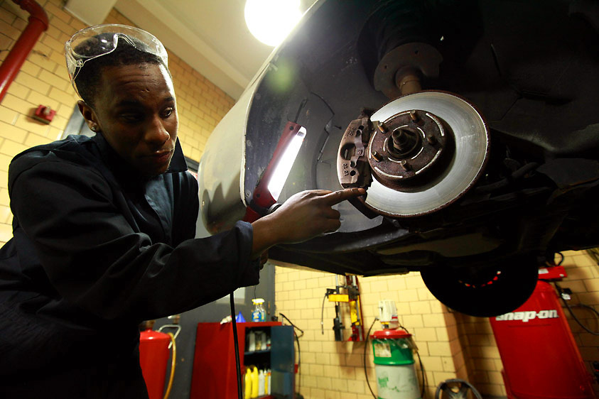 Automotive HS, Brooklyn, NY on Friday, January 22, 2010.  High school students have the opportunity to participate in a special program where they perform basic maintenance and repairs on privately owned cars at very competitive prices.  Student Patrick Grant, 18, points out to a client why he needs new brakes.
