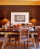 A large print flanked by a pair of lamps and sculpture stands on a console table behind the dining table