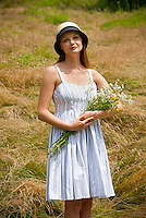 Young woman standing in a field holding a bouquet of wild flowers
