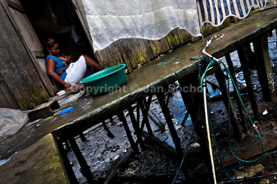A Colombian woman breastfeeds a baby while washing clothes in a bucket, outside a wooden house in the stilt house area in Tumaco, Colombia, 14 June 2010. Although Latin America (as a whole) is blessed with an abundance of fresh water, having 20% of global water resources in the the Amazon Basin and the highest annual rainfall of any region in the world, an estimated 50-70 million Latin Americans (one-tenth of the continent's population) lack access to safe water and 100 million people have no access to any safe sanitation. Complicated geographical conditions (mainly on the Pacific coast), unregulated industrialization (causing environmental pollution) and massive urban poverty, combined with deep social inequality, have caused a severe water supply shortage in many Latin American regions.