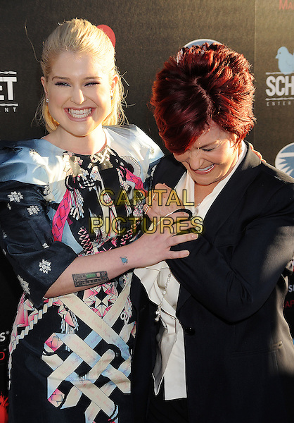 Kelly Osbourne, Sharon Osbourne.'God Bless Ozzy Osbourne' Screening To Benefit The Musicares Map Fund held at the ArcLight Cinerama Dome, Hollywood, California, USA..August 22nd, 2011.half  length black grey gray pink dress print tattoo jacket suit white mother mom mum daughter family tattoos holding hands smiling laughing looking down.CAP/ROT/TM.© TM/Roth/Capital Pictures